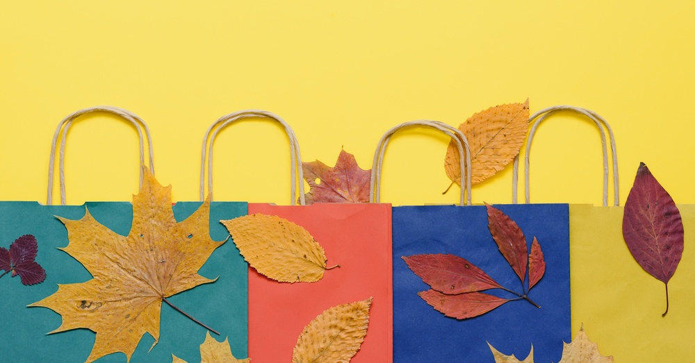 Green, Red, and Blue Shopping Bags Over a Yellow Background With Autumn Leaves